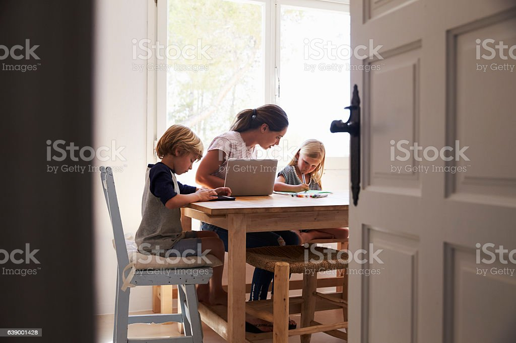 Mum and two kids working in kitchen, close up from Mum and two kids working in kitchen, close up from doorway 20-29 Years Stock Photo