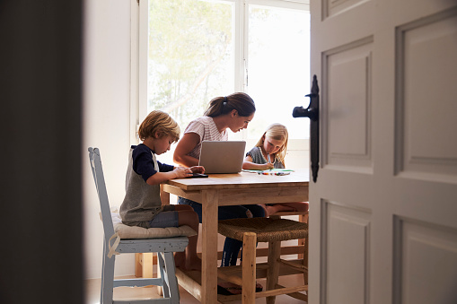 Mum And Two Kids Working In Kitchen Close Up From Stock Photo - Download Image Now