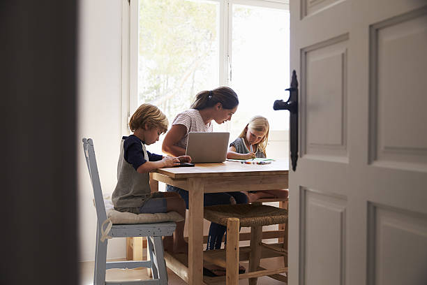 Mum and two kids working in kitchen, close up from Mum and two kids working in kitchen, close up from doorway homework stock pictures, royalty-free photos & images