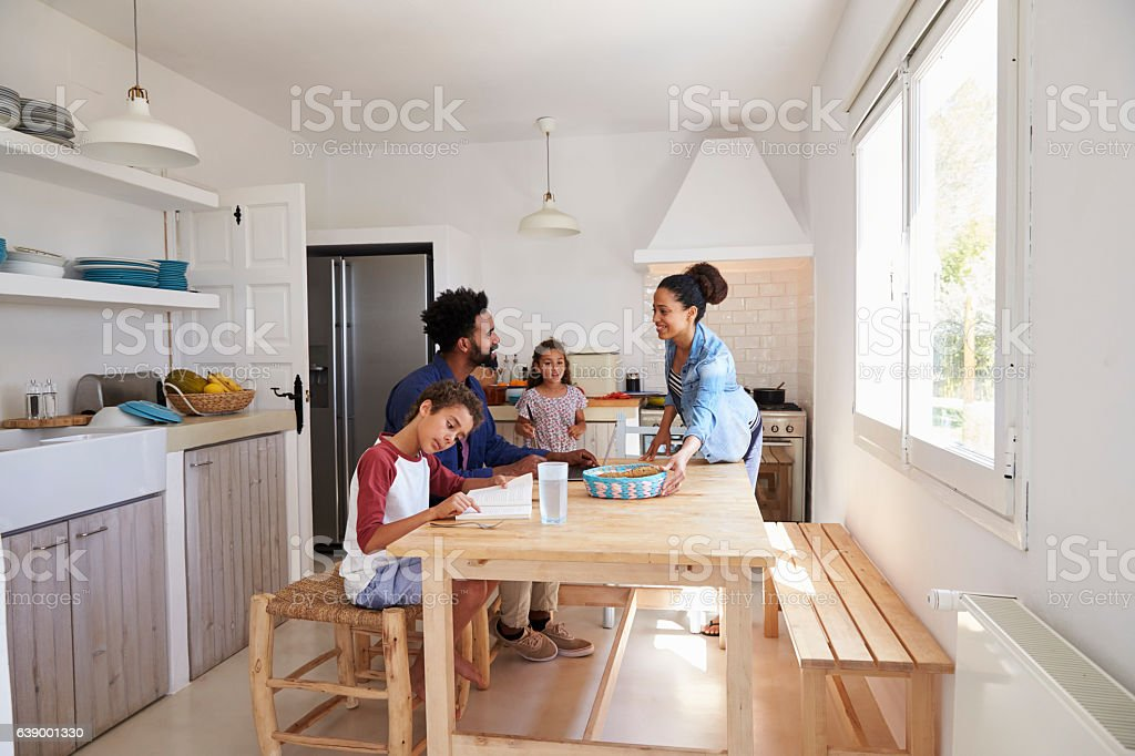 Mum bringing food to the kitchen table for her family stock photo