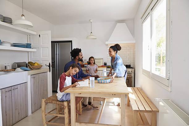 mum bringing food to the kitchen table for her family - küche aus paletten stock-fotos und bilder