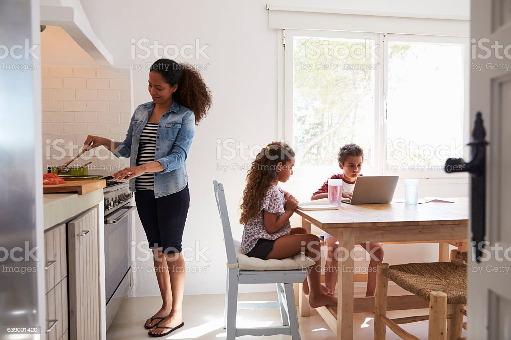 Mum cooking while kids work at kitchen table, from doorway stock photo