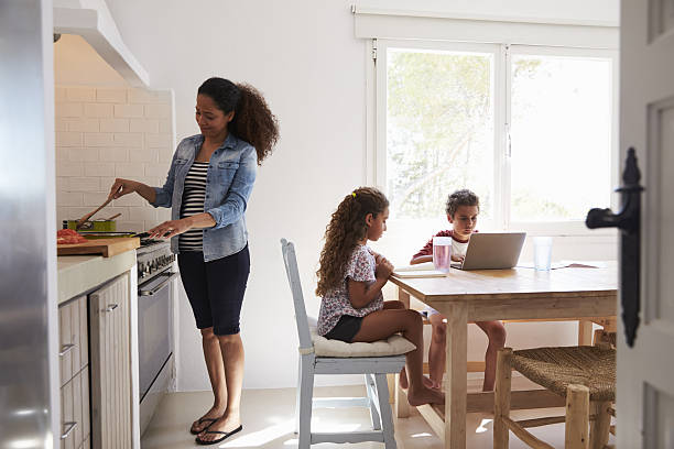 Mum cooking while kids work at kitchen table, from doorway - Photo
