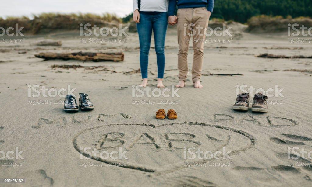 Maman, papa et bébé écrit sur le sable avec les parents derrière - Photo