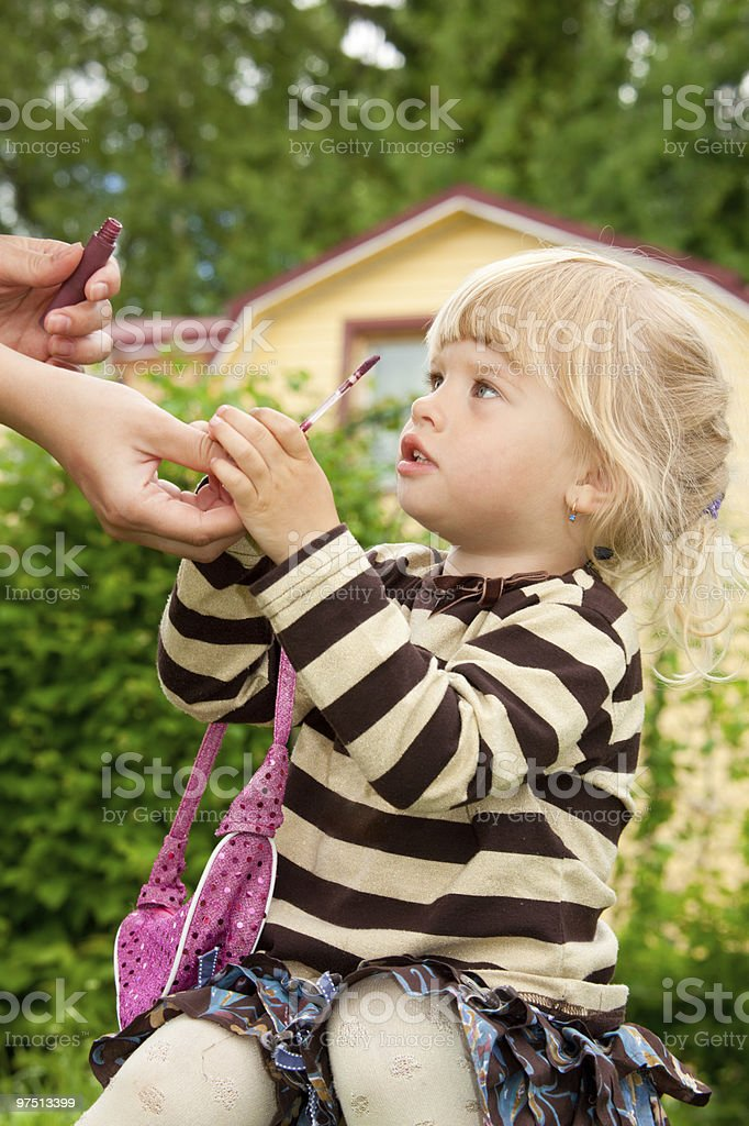 Mum gives to a daughter lipstick outdoor royalty-free stock photo