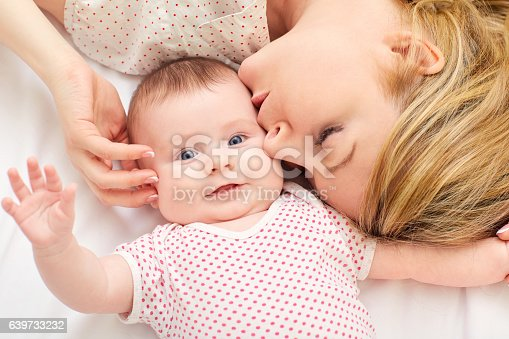 istock Mum kisses baby on the bed 639733232
