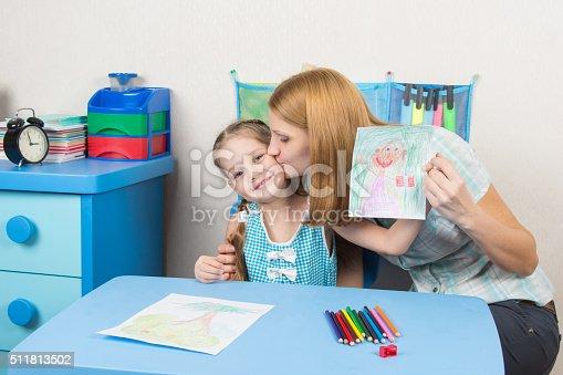 istock Mum kisses the daughter because she drew her beautiful 511813502