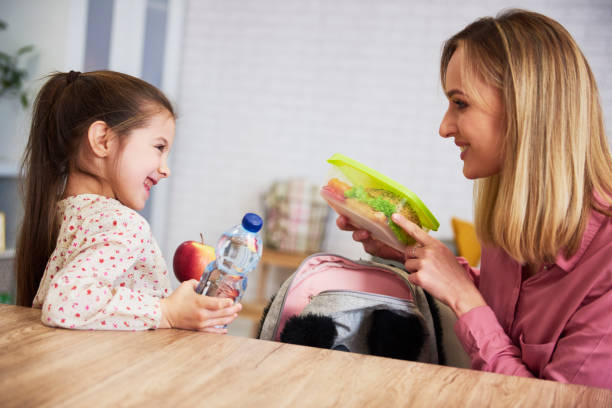 Mum putting lunch box with healthy food in backpack stock photo