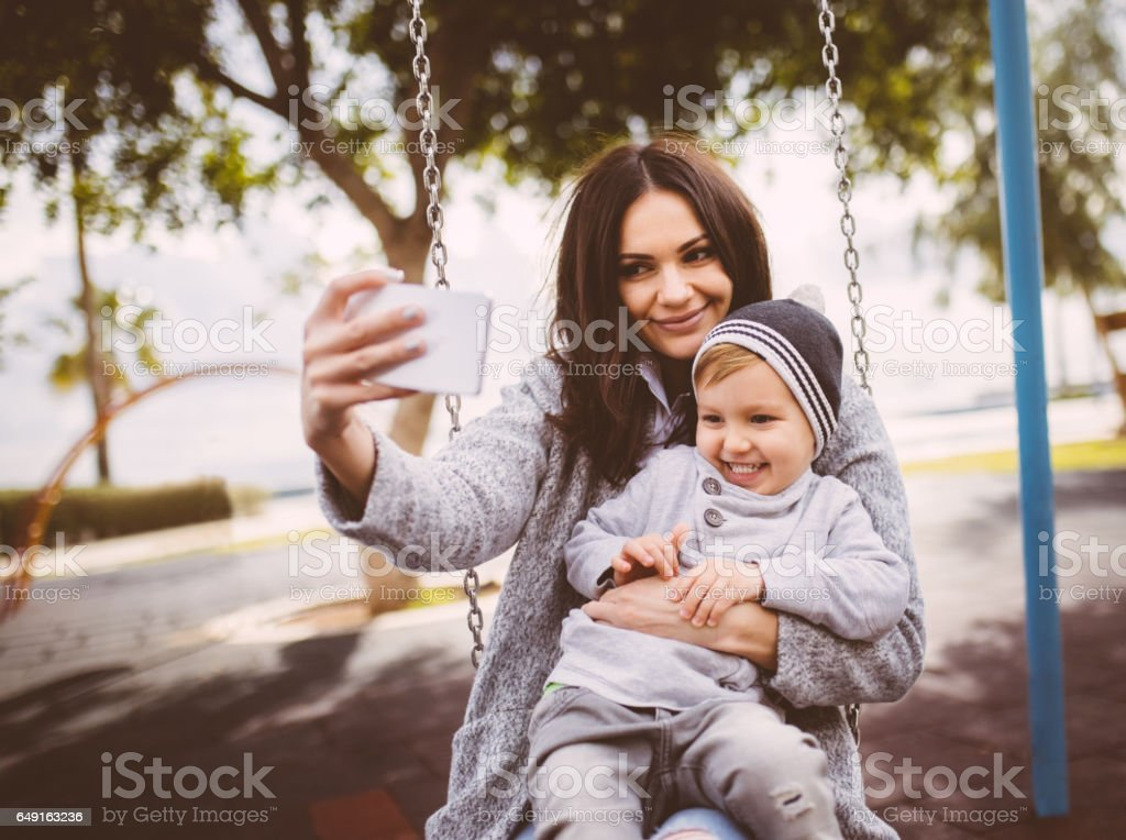 Mum taking a selfie with her son on a swing stock photo