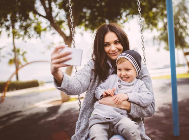 mama nimmt ein selbstporträt mit ihrem sohn auf einer schaukel - lustige babybilder stock-fotos und bilder