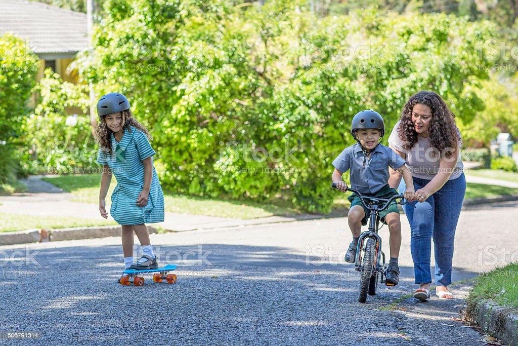 Mum teaching her son to ride a bike stock photo
