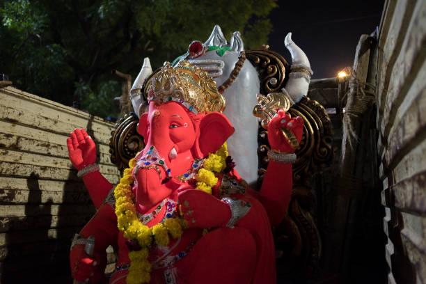 Mumbai, India - 20 september 2019: close up of red hindu god ganesha inside truck during Vinayaka Chaturthi festival celebration in india at night stock photo