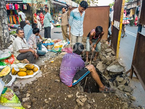 Mumbai, Maharashtra, India - November 2019: Mumbai Municipality labourers dig up a drain by the roadside in the middle of a market street in Kandivali East in suburban MUmbai.