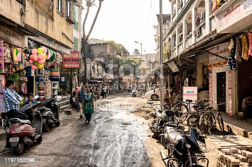 Mumbai, India - December 15th 2019:  People walking on a Mumbai back street, scooters and bicycle parketd, small shops on the sidewalk