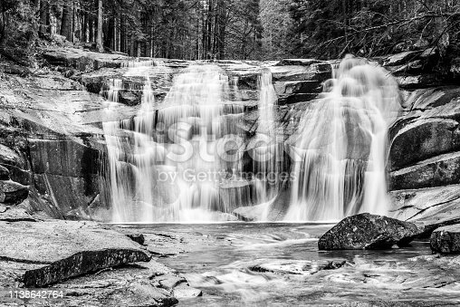 Mumlava waterfall in autumn, Harrachov, Giant Mountains, Krkonose National Park, Czech Republic. Black and white image.
