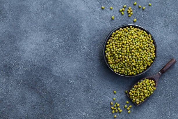 mung bean, green moong dal in wooden bowl. copy space. top view. slate background. - lenticchie verdi foto e immagini stock