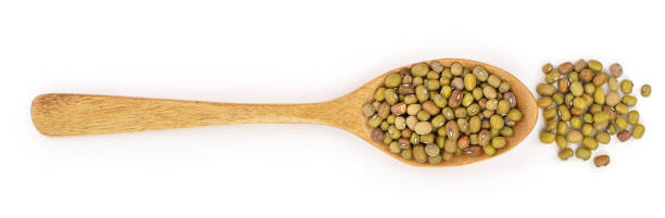 Mung beans in a wooden spoon isolated on white background. Top view stock photo
