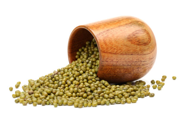 Mung beans in wooden scoop and black bowl isolated on white background stock photo