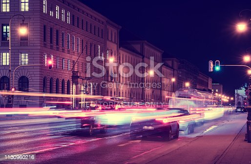 Munich, February 19, 2019 view of Ludwigstraße, facing towards Siegestor: Rushing cars pass a green traffic light whilst hurrying away from the city, creating colorful light trails. The image was processed with cooler, magenta and blue tones to accentuate the feeling of speed and modernity.