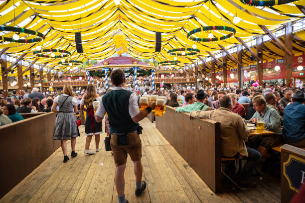 Munich, Germany, Oktoberfest, Waiter holding beers, tent interior background October 7, 2018. Munich, Germany, Oktoberfest, Waiter in tyrolean costume holding beers, tent interior background oktoberfest stock pictures, royalty-free photos & images