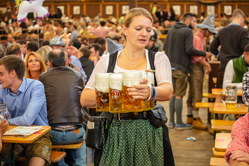 Munich, Germany, Oktoberfest, waitress in tyrolean costume holding beers, tent interior background
