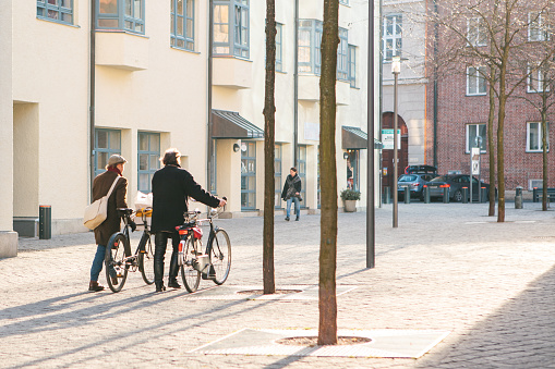 Munich, October 29, 2017: Two men with bicycles walking down the the street