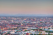 Aerial view of city outskirts in Maxvorstadt and historic center Altstadt in evening sunlight with church towers, densely built residential and commercial buildings and Bavarian Alps in background, Munchen Bayern Germany Europe