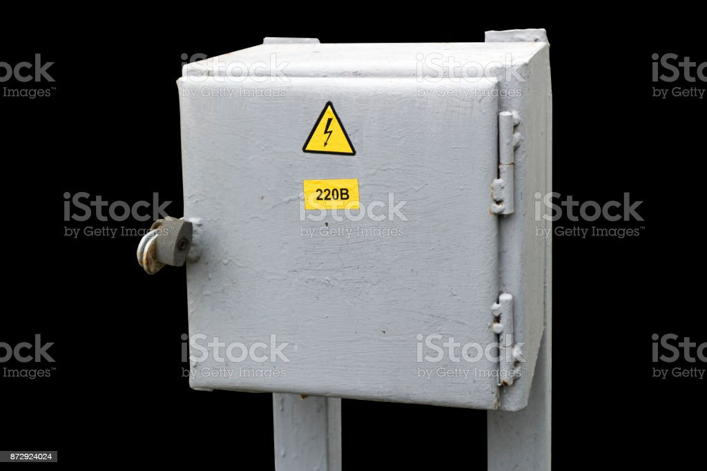 Municipal electrical grey outdoor cabinet with padlock and hazard sign isolated on black. stock photo