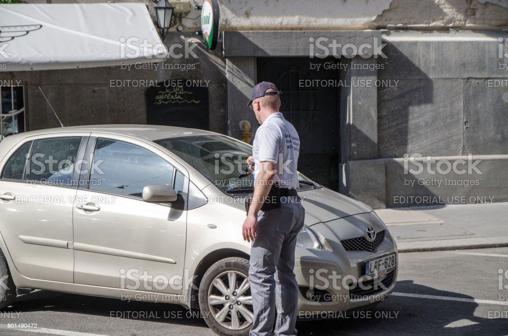 Funcionário municipal, validando o tempo de estacionamento de um carro - foto de acervo