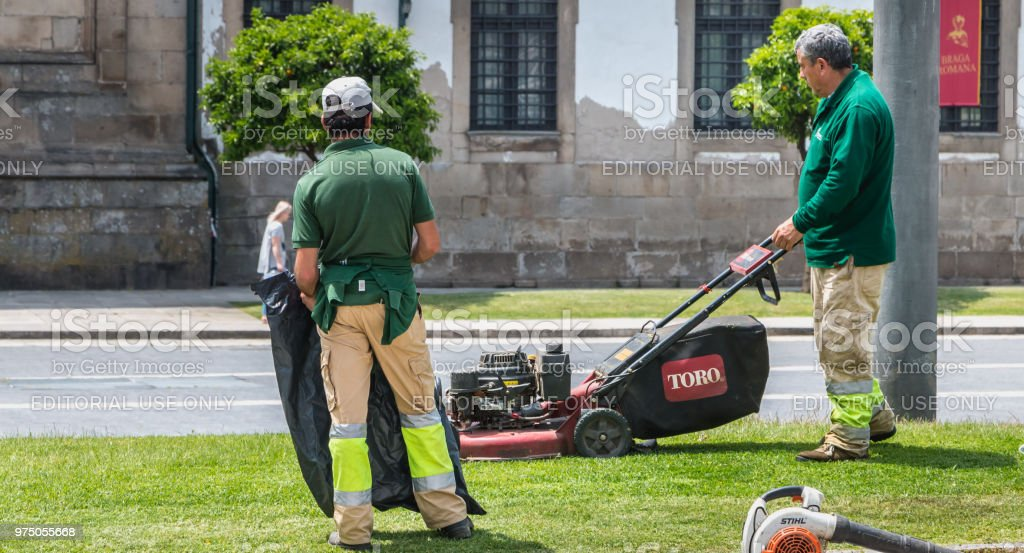 Municipal gardeners mowing the grass in the city center stock photo