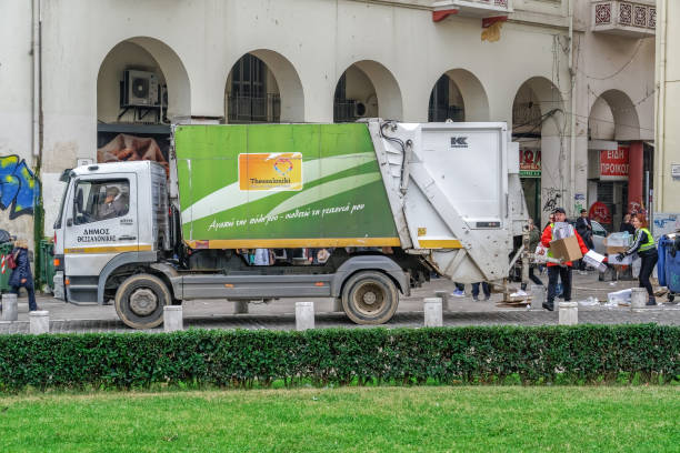 Municipality of Thessaloniki workers collecting garbage and emptying full dumpsters on the city center. stock photo
