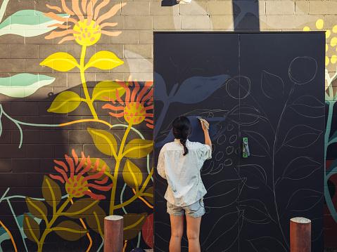 Young Asian woman, mural artist creating wall art at the urban setting.