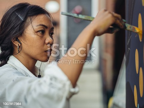 1002918466 istock photo Mural artist at work 1002917364