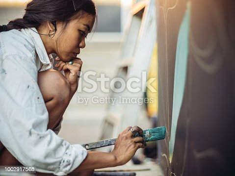 1002918466 istock photo Mural artist at work 1002917568