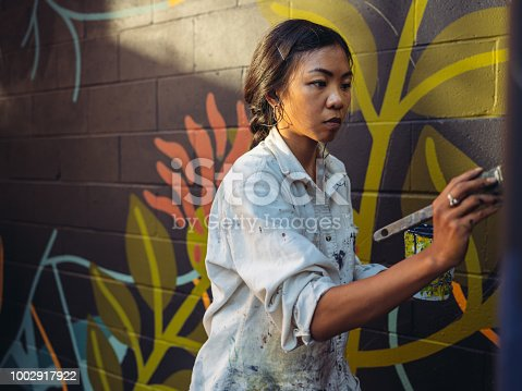 1002918466 istock photo Mural artist at work 1002917922