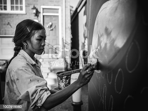 1002918466 istock photo Mural artist at work 1002918560