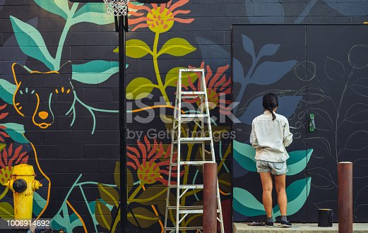 Young Asian woman, mural artist creating wall art at the urban setting.