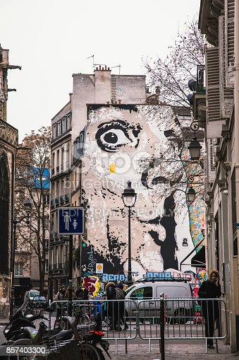 Paris, France - January 25, 2017: Murals painted on the wall of a house. People walking by and working.