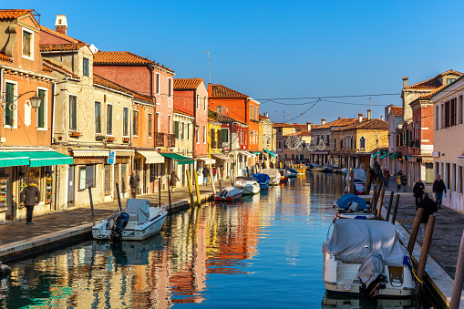 Murano glass making island, water canal, bridge, boat and traditional buildings. Venice or Venezia, Italy, Europe.