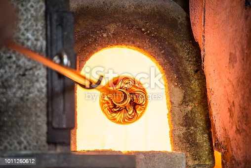 istock Murano glass-blowing factory. Glass blower forming beautiful piece of glass: put iron rod with attached glass object in furnace to make the glass malleable. Italy 1011260612