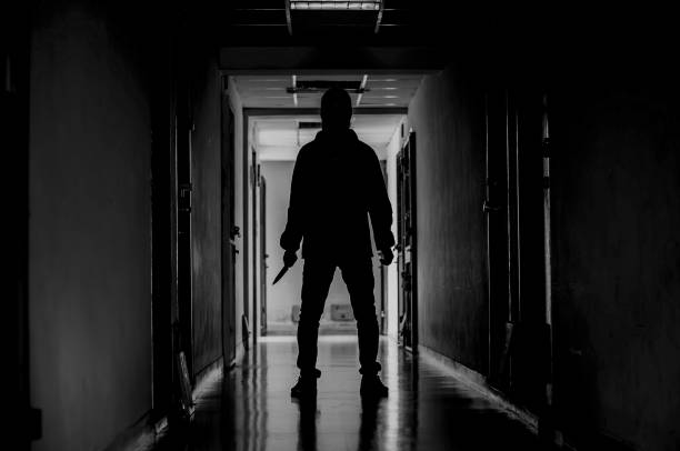 murder, kill and people concept - criminal or murderer wearing a mask in silhouette holding knife inside a condo at crime scene - killer stock pictures, royalty-free photos & images