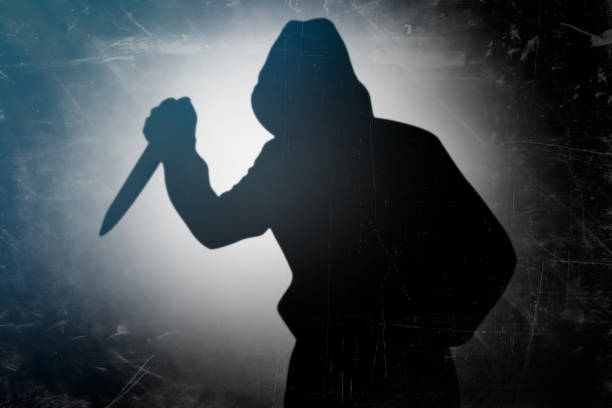 Murderer holding knife in his hand stock photo