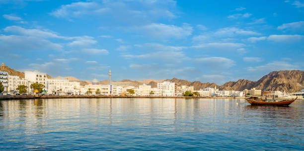 muscat skyline with a traditional arabic dhow anchored at the port - oman zdjęcia i obrazy z banku zdjęć