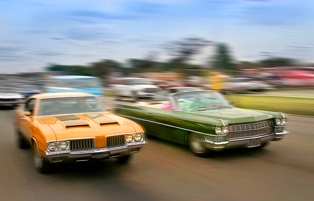 Muscle Cars Orange and green color muscle cars cruising on historic woodward avenue. car show stock pictures, royalty-free photos & images
