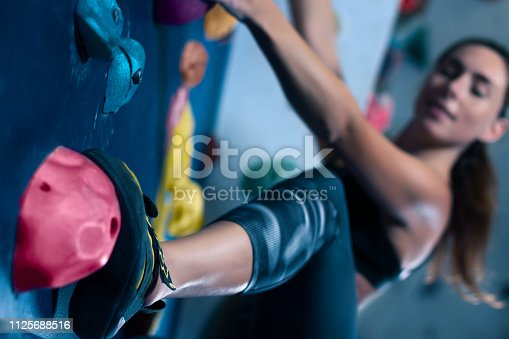 istock Muscle female woman climbing bouldering in training hall 1125688516