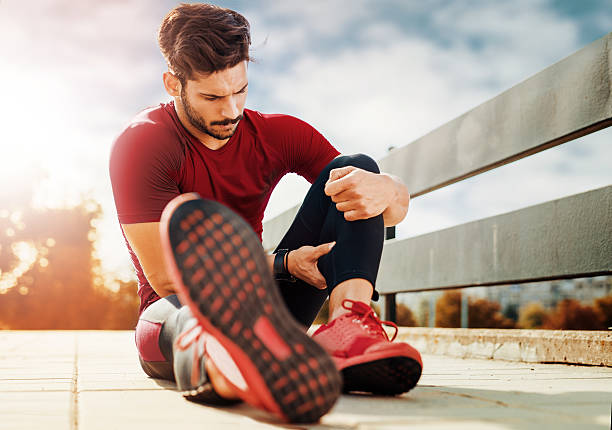 Muscle injury Portrait of a muscle fitness man reaching for his leg in pain human leg stock pictures, royalty-free photos & images