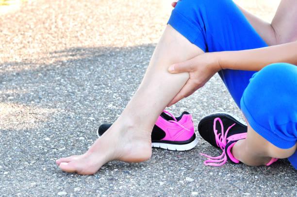 muskelverletzung. laufende verletzung beinverletzung unfall-sportlerin verletzt schmerzhafte bein. die athletenfrau hat muskelverletzungen, versprüht das bein beim lauftraining in der natur. - schlanke waden stock-fotos und bilder