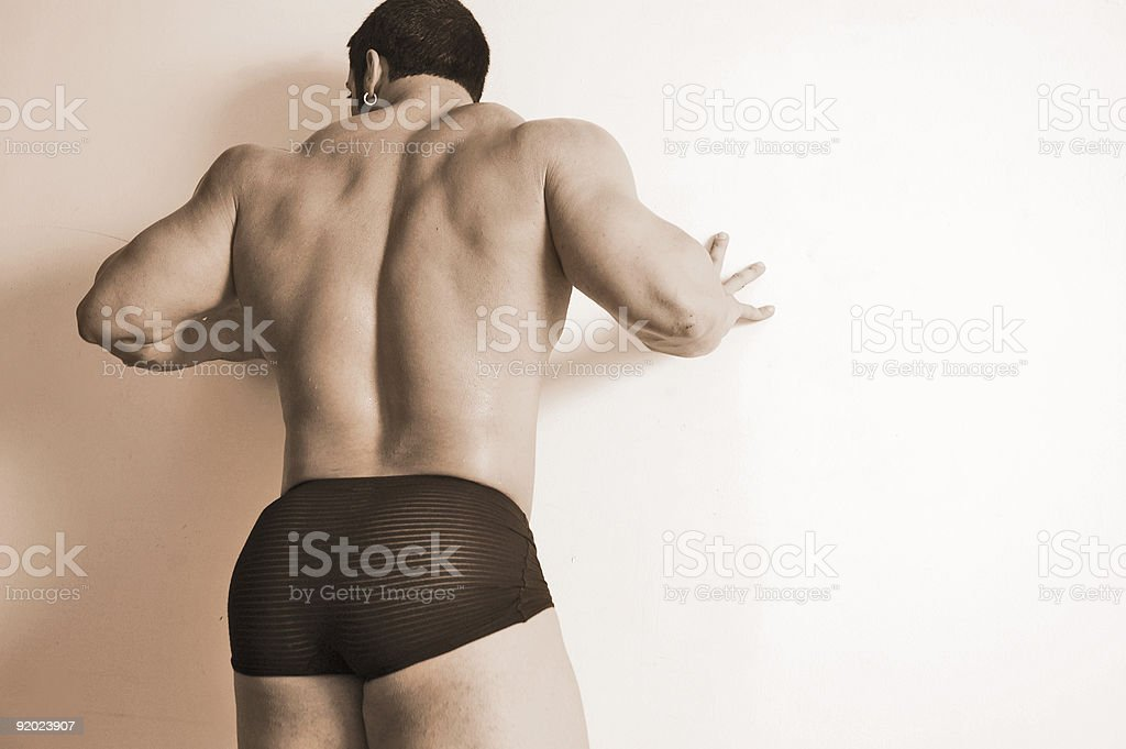 Muscle man against wall stock photo