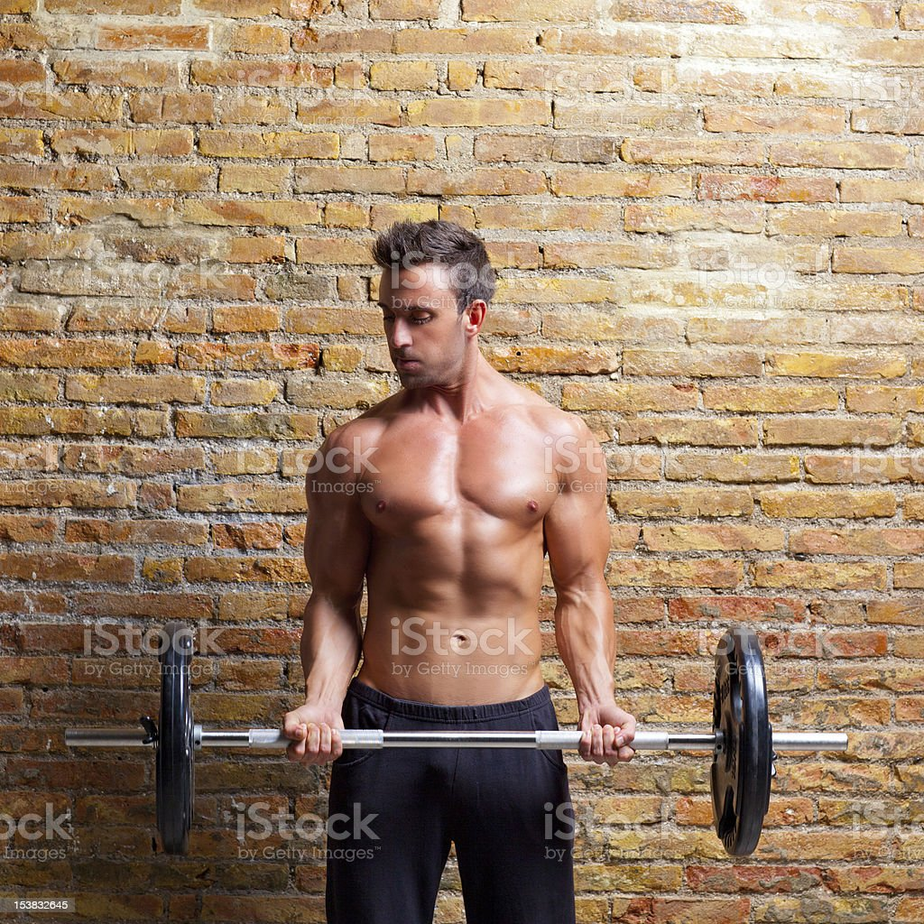 muscle shaped body man with weights on brick wall royalty-free stock photo