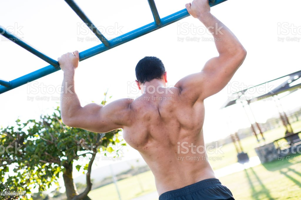 Muscle up! back of young man doing muscle-ups in public park stock photo